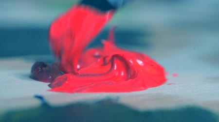 escovado : Paint red are mixed with a brush close-up. Brush smear oil paint on a surface close up. Blue tone Vídeos