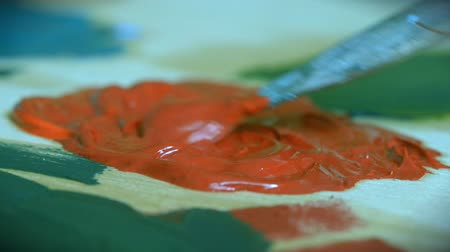 tahy : Paint red are mixed with a brush close-up. Brush smear oil paint on a surface close up