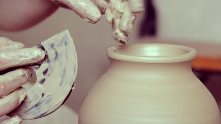 oleiro : Making Crock crude wet close-up. Man hands and tool making clay jug macro. The sculptor in the workshop makes a jug out of clay closeup. Vase of white clay crude wet closeup,