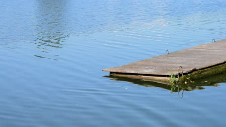 shabby : Wooden dock on the water close-up on calm sunny day