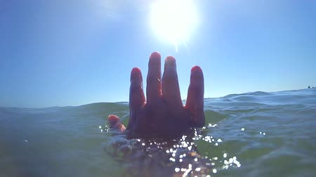 sos : Slow motion POV. The hand of the man who sinks drowning, the hand rises and falls over the sea level close-up, clear cloudless blue sky, sun and transparent clear water. Wide angle