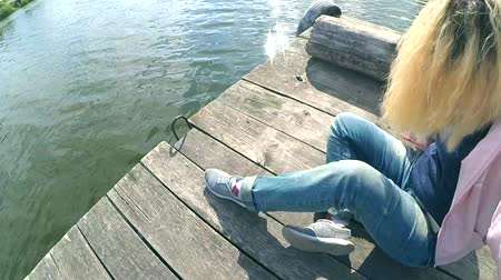 inclinado : Blond girl in blue jeans sits on the edge of an old wooden pier berth dock near the lake pond with inclined head close-up on sunny day. Rest relax on the nature near the water. Concept