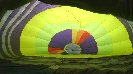 dobrado : Inflation of large balloon aerostat that lies on ground. Preparation of flight air balloon for flight. Inside view close-up. Balloon or aerostat green and multicolor inflated with air by fan blower