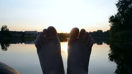 фут : POV Black silhouette of feet moves it in air, through fingers rays of sun during Orange yellow sunrise sunset dawn near lake pond. Rest relax vacation holiday. Rest happiness fun relax summer concept