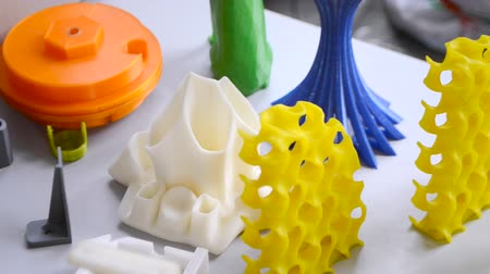 modelagem : Many bright multi-colored objects printed on 3d printer lie on flat surface close-up. Fused deposition modeling, FDM. Concept modern progressive additive technology for 3d printing.