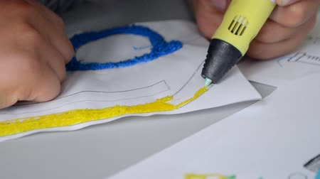 persone : A persone drawing 3d pen close-up. The plastic thread melts under the influence of the temperature inside the stream and flows out with a liquid thread that hardens in the air