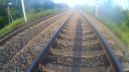 sleepers : POV. The girl is walking along the center of the railway tracks, the sun is shining in the back, shadow of a man walking on a railway.