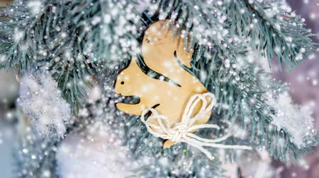 gif : Christmas tree toys decorations and snow-covered Christmas tree branches close-up with snowfall, falling snowflakes, spots white color. Winter Christmas New Year background. Cinemagraph seamless loop