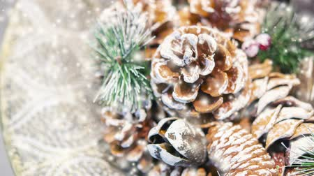 gif : Natural Christmas New Years toy pine cone and Christmas tree branch close-up. Snowfall, falling snowflakes, spots white color. Winter Christmas New Year background. Cinemagraph seamless loop