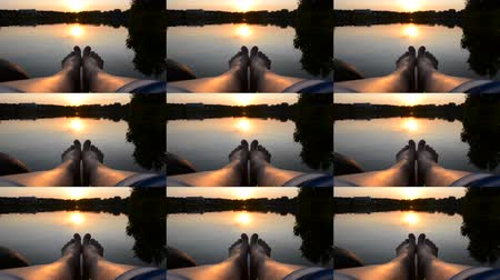 嘘 : Feet legs lie on pier near lake pond at sunset dawn sunrise close-up. Smooth water surface on which the sun is reflected, windless weather. Black strip of the horizon. POV, point of view. Wide angle. 動画素材