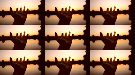 arms in the air : POV Black silhouette of hand moves it in air, through fingers rays of sun during Orange yellow sunrise sunset dawn near lake pond. Rest relax vacation holiday. Rest happiness fun relax summer concept