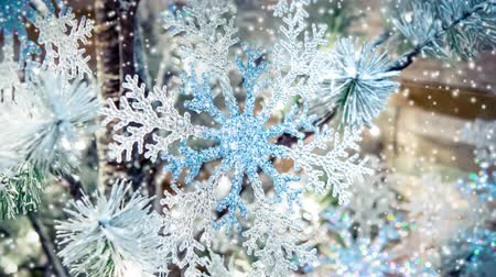 decorating : Transparent Snowflake Decor New Year Christmas Decoration, Christmas tree branch green spruce needles, Christmas-tree toys, snow snowfall snowstorm snowflakes. Winter Christmas New Year background Stock Footage