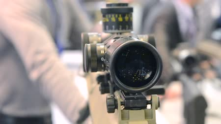 barril : Weapon optics sight of sniper rifle with a man in the back blurred background close-up in the store or shop.