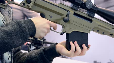 armaments : Weapon optics sight of sniper rifle with man close-up in store or shop. Firearms gun submachine sniper rifle large-caliber weapons close-up.