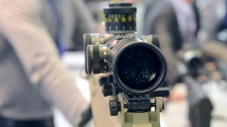 submachine : Weapon optics sight of sniper rifle with man close-up in store or shop. Firearms gun submachine sniper rifle large-caliber weapons close-up.