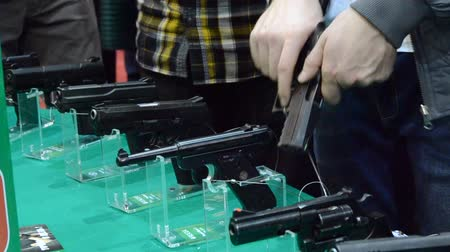 калибр : Several large-caliber weapons on the table. Person holding a gun in hand close-up. Firearms gun submachine sniper rifle large-caliber weapons close-up.