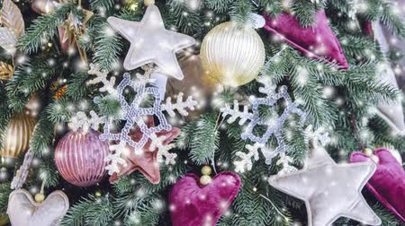 gif : Different decorative Christmas-tree toys close-up, decorations for Christmas tree, green spruce branch needles, snow snowfall snowstorm snowflakes. Winter Christmas New Year background. Cinemagraph