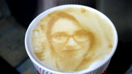варивший : Drawing of a womans face on a foam coffee latte in a glass created by a 3D printer close-up. 3d printer created a portrait of a girl on the foam of brewed coffee