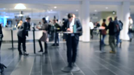 behind bars : Blurred Background. People are standing behind counter in of white hall. People in black business suit standing in space and communication. Crowd lot of people. Gray blurred Abstract Background Stock Footage