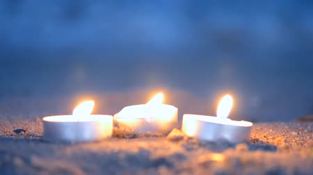 sea breeze : Three small candles tablets lie on a sandy beach near the waves with foam lapping on shore in the evening close-up. Romance mood background Stock Footage