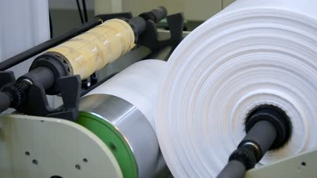gyártó : Plastic bag making machine close-up. A plastic bag is wound on a large spool or reel Stock mozgókép