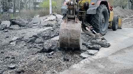 приложение : Old tractor bucket breaking asphalt. Technical city works. Repair urban work close-up