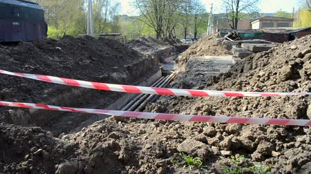 törmelék : Large pit dug in the ground for the purpose of order remot and for laying water pipes of city communications fenced with a protective red tape, on construction site