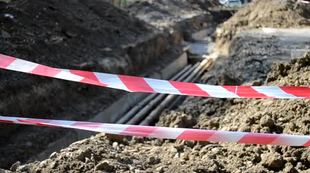 cloture : Large pit dug in the ground for the purpose of order remot and for laying water pipes of city communications fenced with a protective red tape, on construction site