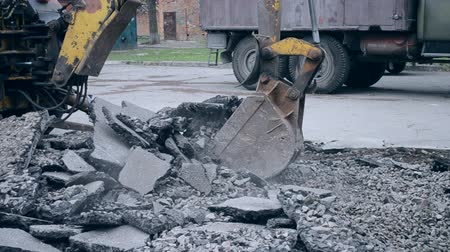привязанность : Old tractor bucket moves pieces of broken asphalt. Tractor removes broken asphalt construction site. Technical city works. Repair urban work close-up. Outdoors city works