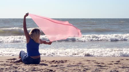 kum saati : Girl with a pink scarf is sitting on the sandy shore of the beach near the sea on a sunny warm summer day. Sea rest seascape view relax sealandscape Stok Video