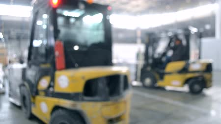 hangar : Construction works inside large building. Building installation exhibition center. Loader machine on the construction site. Many people in installation work. Blurred Background