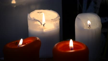 信仰 : Four paraffin candles are burning at night close-up.