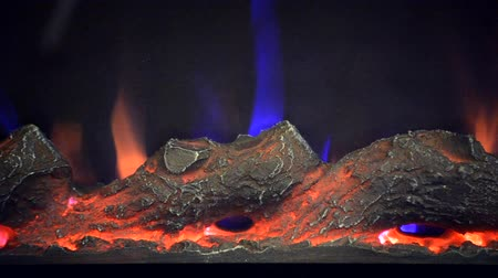 hearth : Artificial electrofireplace glowing backlight close-up. Artificial yellow flame. Artificial black firewood.