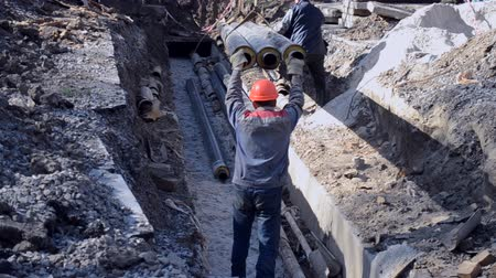 emel : Workers with construction crane put new water pipes with concrete slabs into ground on construction site. Technical city works. Repair urban work close-up. Stock mozgókép