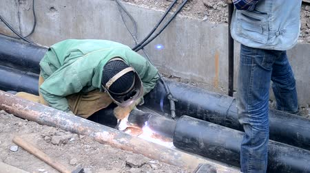 шов : Welding seam of new water pipes. Welding the joint of new water pipes at the construction site. Industrial worker in protective mask using welding machine for welding metal construction