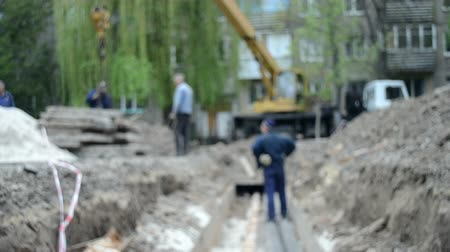 kladkostroj : Blurred Background. Workers with construction crane cover new water pipes with concrete slabs into ground on construction site. Technical city works. Repair urban work close-up. Dostupné videozáznamy