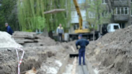 emel : Blurred Background. Workers with construction crane cover new water pipes with concrete slabs into ground on construction site. Technical city works. Repair urban work close-up. Stock mozgókép