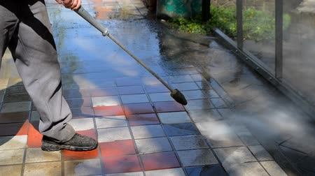 cúbico : Street cleaning pressure water. Man worker cleaning city dirty streets with high pressure and temperature industrial and communal washer. Park on sunny day. High power professional cleaning Stock Footage