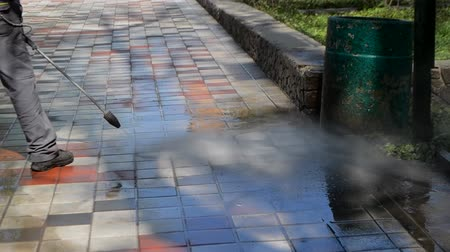 tryska : Street cleaning pressure water. Man worker cleaning city dirty streets with high pressure and temperature industrial and communal washer. Park on sunny day. High power professional cleaning Dostupné videozáznamy