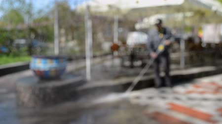 yıkayıcı : Blurred Background. Street cleaning pressure water. Man worker cleaning city dirty streets with high pressure and temperature industrial and communal washer. High power professional cleaning
