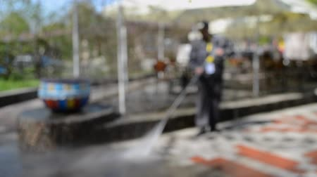 arruela : Blurred Background. Street cleaning pressure water. Man worker cleaning city dirty streets with high pressure and temperature industrial and communal washer. High power professional cleaning