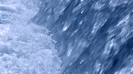 vazamento : Clean blue water falls under strong pressure. Flow of water with white foam close-up. Strong current Stock Footage