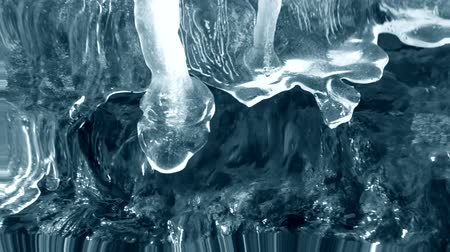 dangle : Thawing of ice on the edge of a waterfall brook close-up. With sound. Conceptual Nature Background, Blue color. Reflection in water, underwater water ripples surrealism abstract