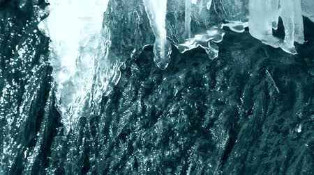 dangle : Thawing of ice on the edge of a waterfall brook close-up. With sound. Conceptual Nature Background, Blue color. Clean blue water falls under strong pressure. Flow of water close-up.