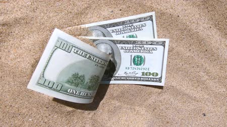 recessione : money dolars half covered with sand lie on the beach close-up Filmati Stock
