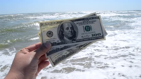 kavramak : Girl holding a money bill of 300 dollars on a background of sea waves and sky on sunny day. Hand waves sea ocean money dollars bills relax vacation relax sun summer. Concept holiday relax vacation