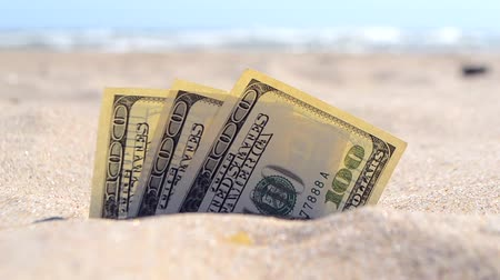 gömülü : Money dolars half covered with sand lie on beach close-up. Three hundred dollars buried in sand on sea or ocean beach Concept finance money holiday relax vacation. Sunny summer warm wind day.