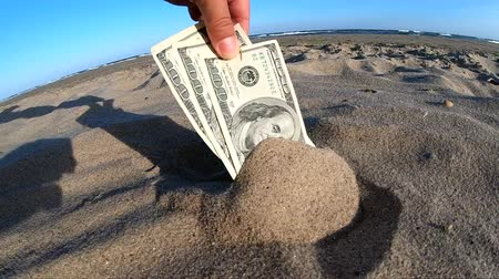 buried : A girl takes out from the sand money notes of three hundred dollars. Concept finance money holiday relax vacation. Sunny summer warm day. A man takes out dollars from sand buried money banknotes