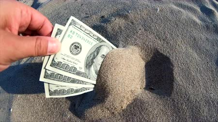 cenný : A girl takes out from the sand money notes of three hundred dollars. Concept finance money holiday relax vacation. Sunny summer warm day. A man takes out dollars from sand buried money banknotes