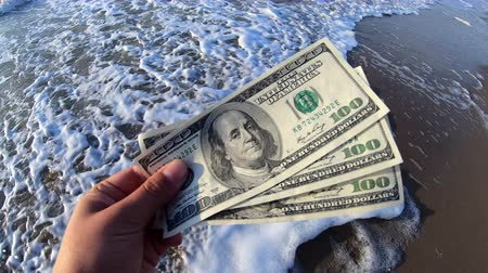 сцепление : Girl holding a money bill of 300 dollars on background of sea waves on sunny day. Hand waves sea ocean money dollars bills vacation relax sun summer. Concept holiday relax vacation. Windy wind